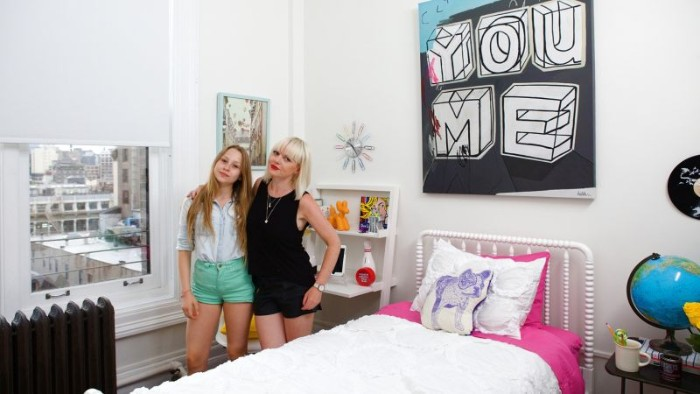 mother and daughter, hugging in a room, with white walls, a large black and white artwork, and a small single bed, in white and pink