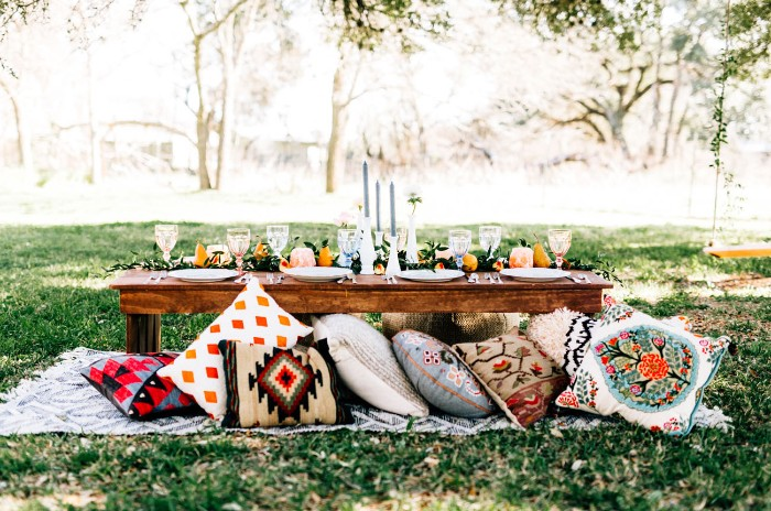 cushions in various colors, with different patterns, next to a wooden table, decorated for a fancy meal, and placed in a garden, 50th birthday ideas