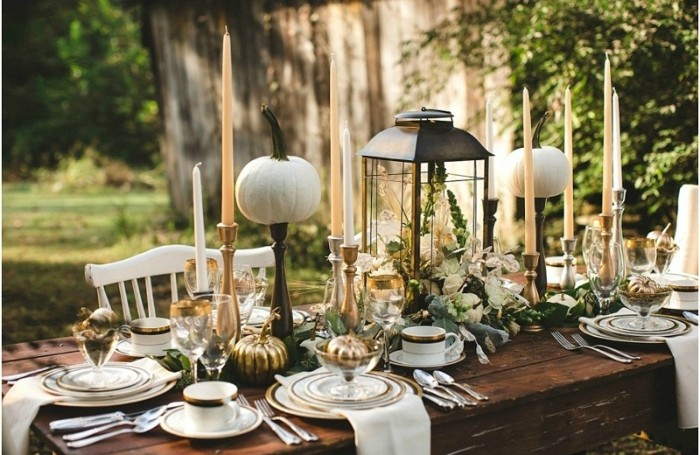 garden thanksgiving table setting, dark brown wooden table, decorated with pumpkins, a lantern filled with flowers, and several tall candles, plates and cups, cutlery and white napkins