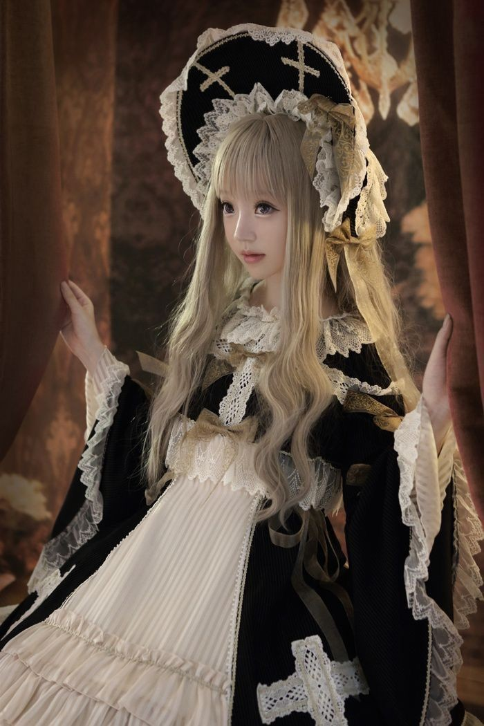 cross motifs on a black bonnet, decorated with white lace trims, worn by a girl, in a long ash blonde wig, with a black and white lolita dress, featuring bell-shaped sleeves, frills and bows