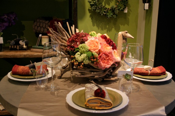 peach pink roses, dark red and light green flowers, in a wooden basket, shaped like a turkey, placed in the center, of a brown round table