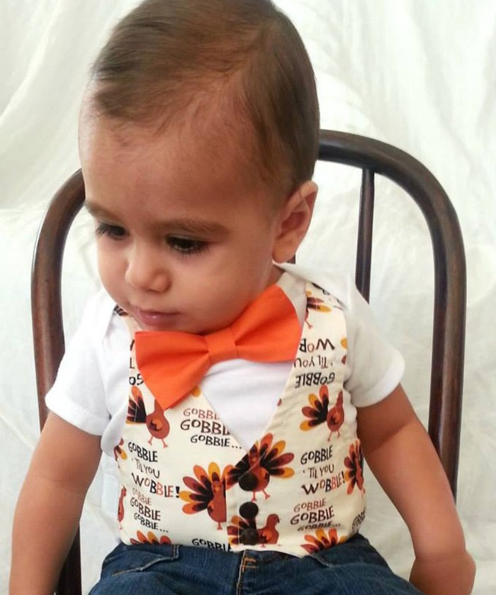 vest in white, with a cartoon turkey pattern, worn with an orange bow tie, over a white t-shirt, baby's first thanksgiving outfit, for infant boys