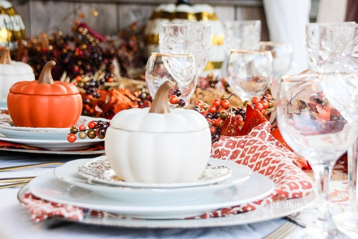 pots in the shape of pumpkins with lids, in white and orange, thanksgiving table decorations, plates and glasses, decorative fall leaves and berries