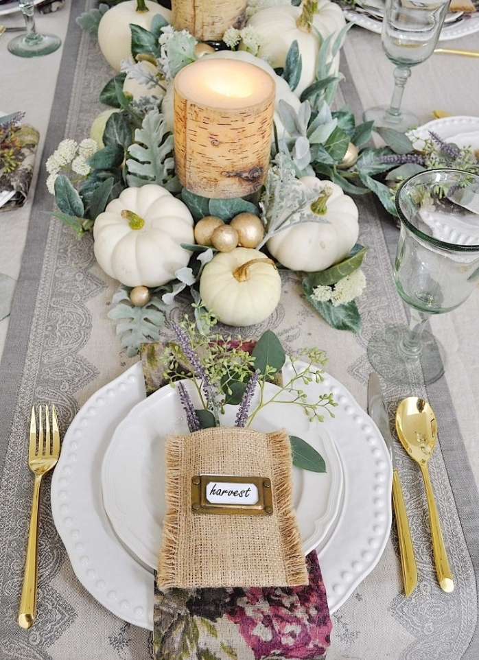 pouch made of burlap, with a small name tag, placed on top of two white stacked plates, surrounded by gold cutlery, thanksgiving table setting, candles surrounded by leaves, small white pumpkins, and gold baubles