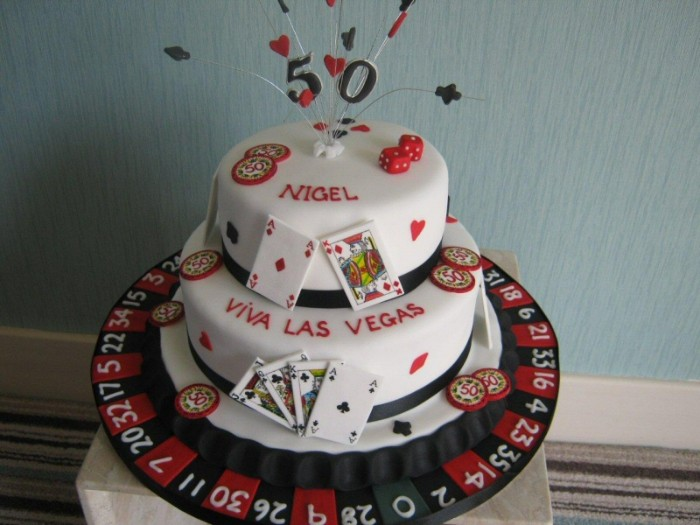 roulette and gambling chips, made from black and red fondant, decorating a white cake, with a 50 topper, dice and playing card symbols, 50th birthday party ideas for men, las vegas casino