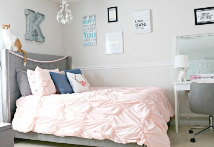 headboard in grey, attached to a bed with multiple cushions, and a pale powder pink bed cover, cool beds for teens, posters and a desk, with a grey chair