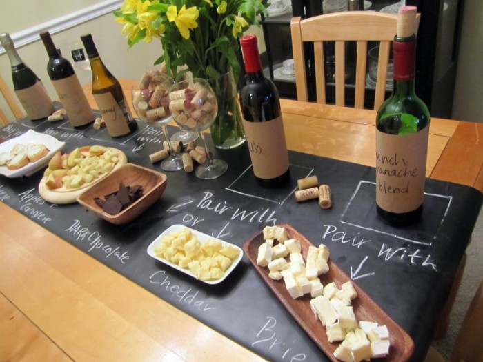 chockolate and apples, different kinds of cheese, and other snacks, near five bottles of wine, 50th birthday themes, wine tasting experience