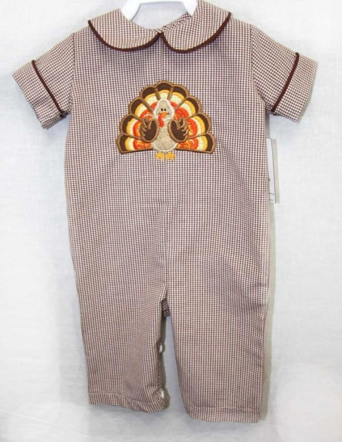 peter pan collar, and short sleeves, on a checkered onesie, in brown and white, embroidered with a turkey cartoon, baby's first thanksgiving outfit, on a whiite background