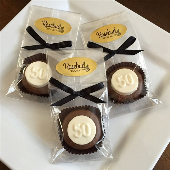 individually packaged brown and white chocolates, each featuring the number 50, and a black ribon tied in a bow, birthday party favors