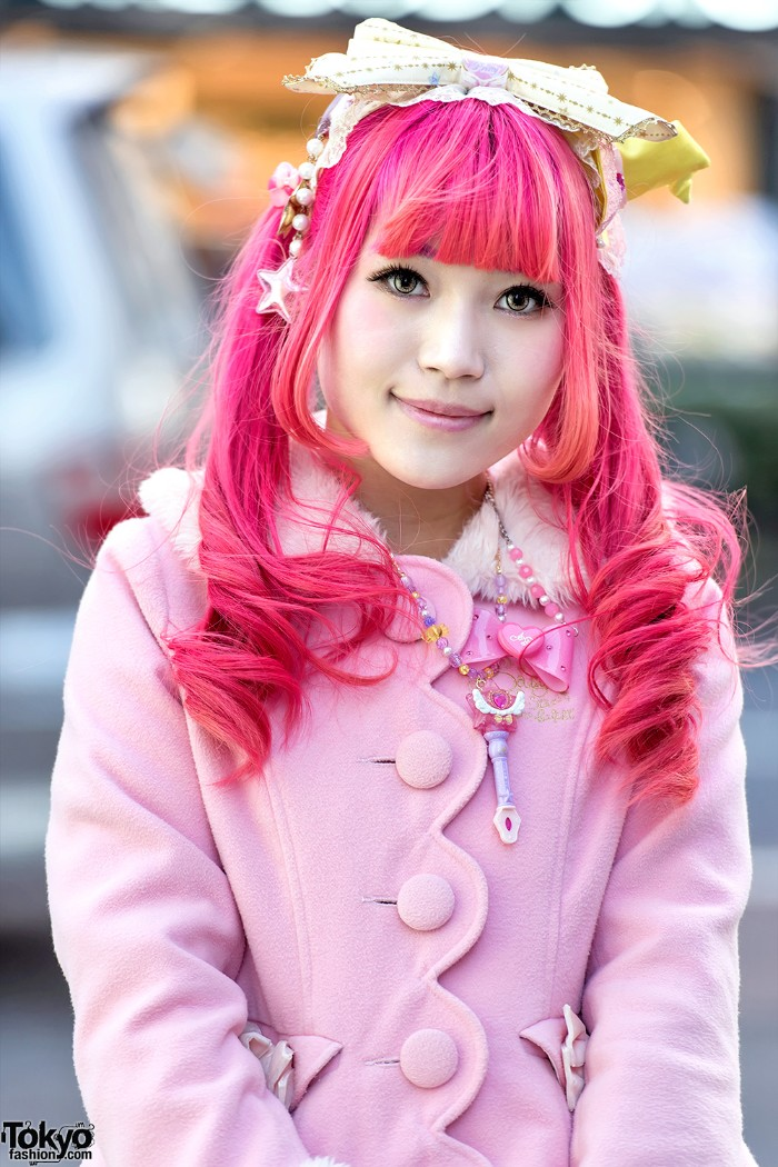 hot pink wig, with straight bangs and curls, on a smiling girl, dressed in a pastel pink, lolita fashion coat