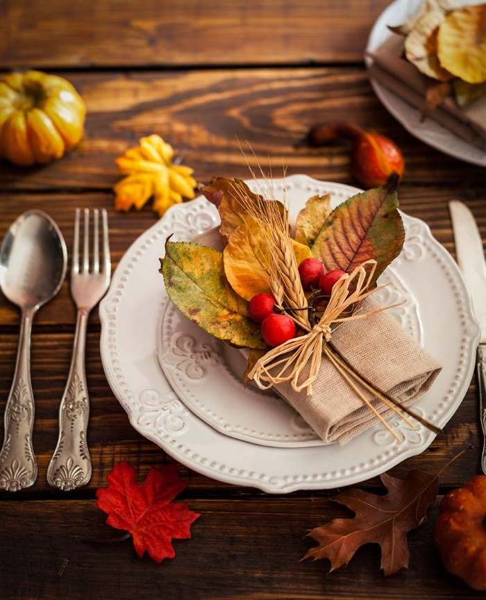 napkin made of burlap-like material, decorated with fall leaves, red berries and two sprigs of wheat, tied with paper rope, and placed on a white plate, thanksgiving table setting, silver vintage-style cutlery