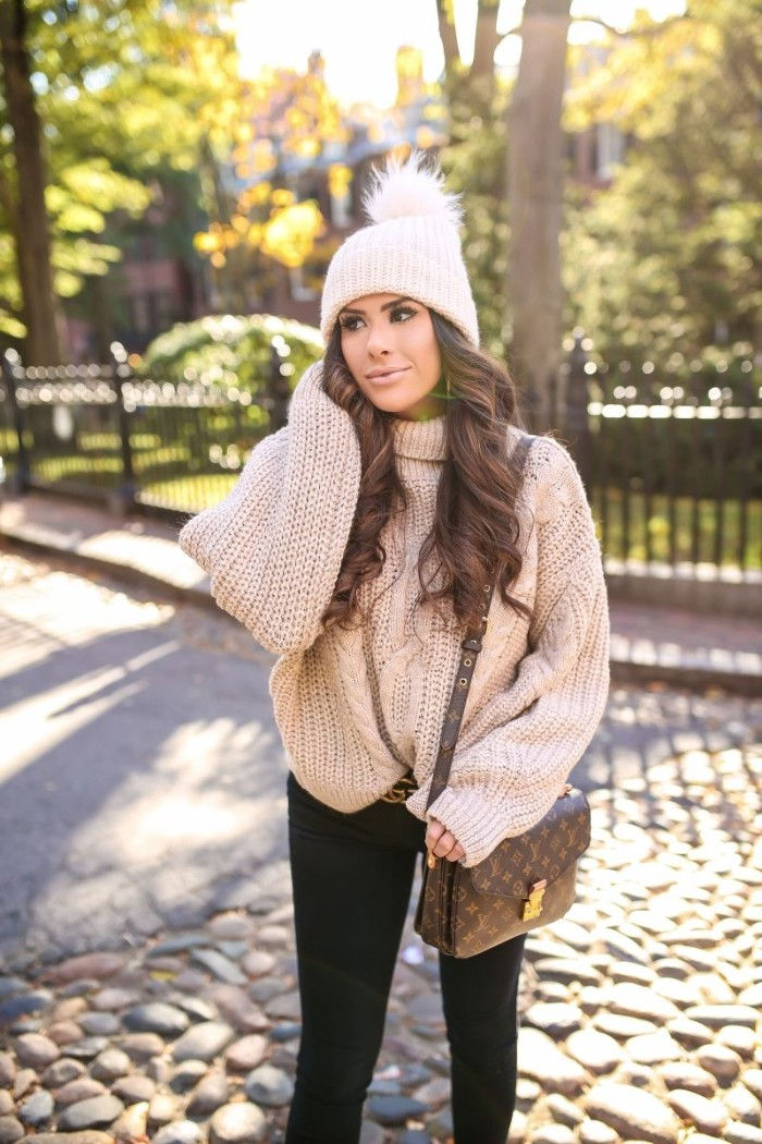 fluffy pom pom, on a pale cream knitted hat, worn by a young brunette woman, with long curled hair, thanksgiving outfits, oatmeal chunky knit jumper, black skinny jeans, and a designer shoulder bag