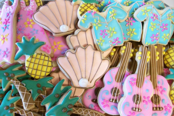 assortment of cookies, shaped like shells and dresses, guitars and pineapples, shirts and palm trees, decorated with colorful frosting and edible pearls, 50th birthday colors