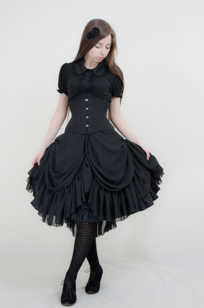 brunette woman with long smooth hair, dressed in a black corset, over a black tiered dress, lolita fashion, black knitted tights