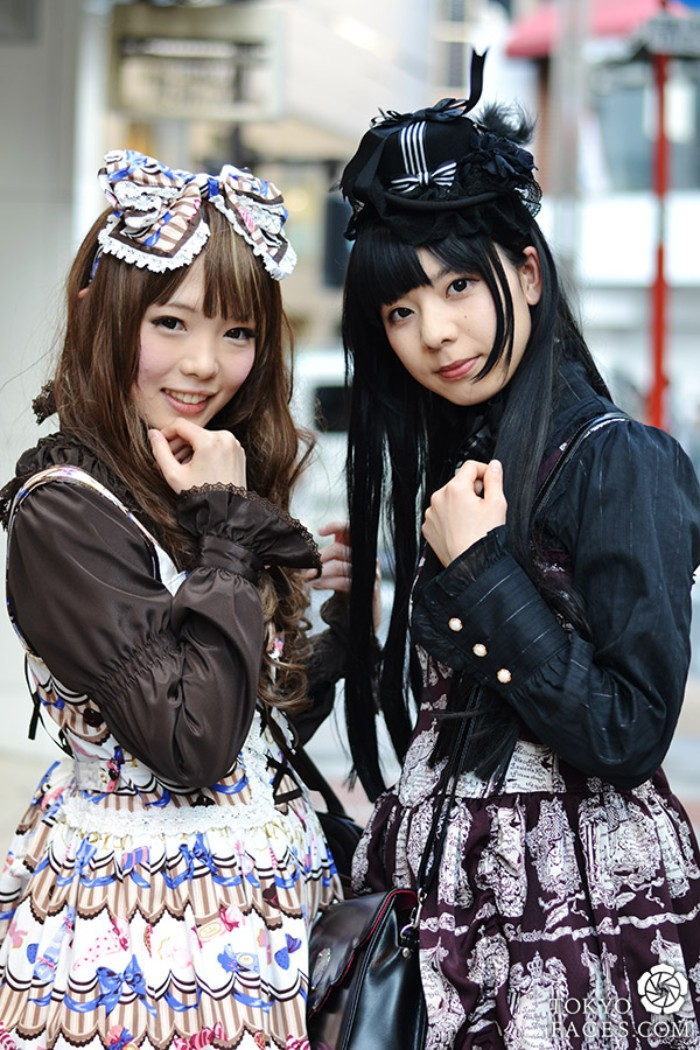 two girls dressed in gothic lolita dresses, brown and black shirts, worn under patterned pinafores, a large bow and a black hat