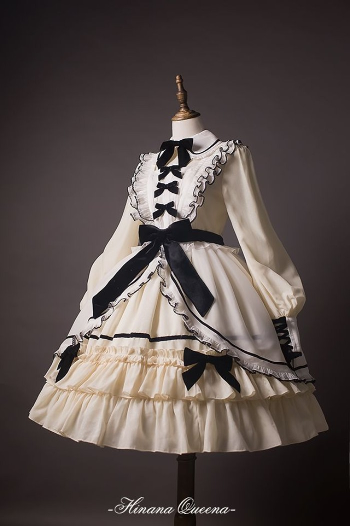 define lolita, dress in white and cream, decorated with multiple black bows, and featuring frills, a peter pan collar, and a lace bib detail
