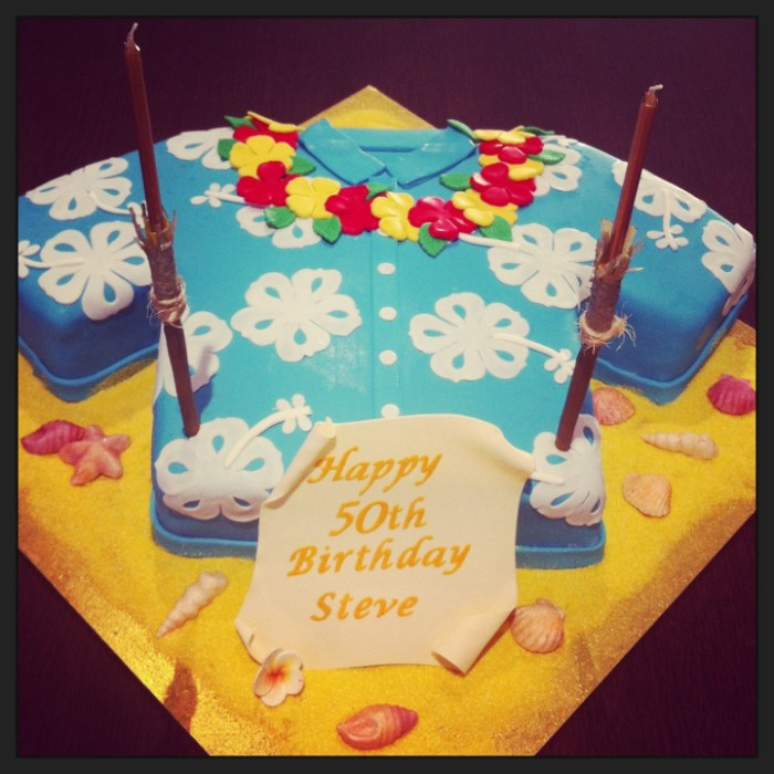 cake shaped like a shirt, pale blue with white floral hawaiian-style print, and a flower garland made from yellow and red fondant, 50th birthday colors, for a hawaiian themed party