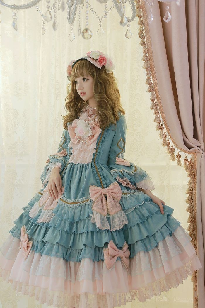 baroque inspired dress, in pale blue, with a tiered skirt, light peach pink bows, and lots of white lace, worn by a pale and slender girl, with light brunette hair