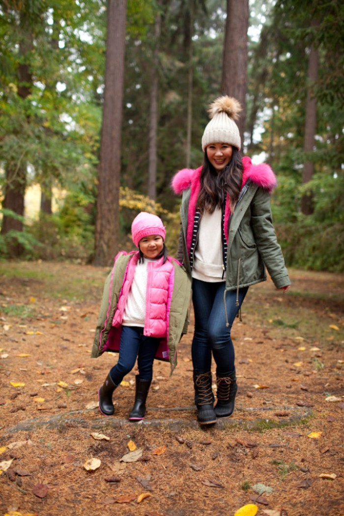 matching outfits for moms and daughters, skinny dark blue jeans, white jumpers and pale green parkas, toddler thanksgiving outfit ideas, on a little girl, standing next to her mom, in the forest