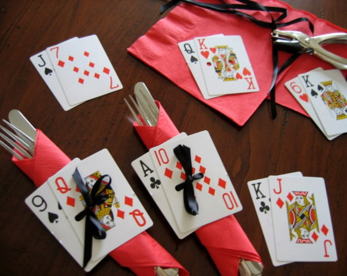 forks and knifes, wrapped in red paper napkins, decorated with playing cards, tied to them with black ribbons, 50th birthday party ideas for men, table set up and decorations