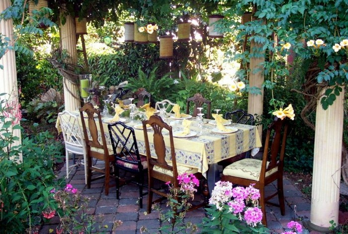flowers and other plants, and several white columns, surrounding a festive table, with several different chairs, 50th birthday party ideas for mom, dinner in the garden