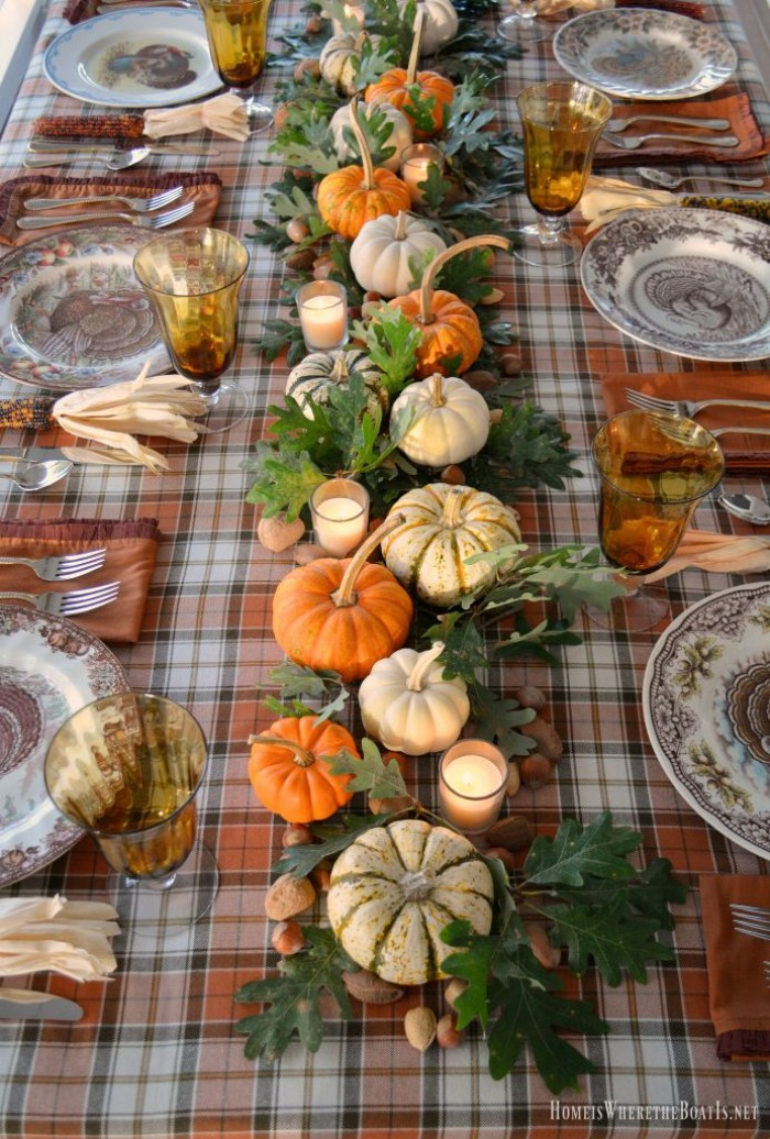 plaid tablecloth in orange, brown and white, on a rectangular table, decorated with orange, white and cream pumpkins, and dark green leaves, thanksgiving tablescape, ornamental plates and borwn napkins