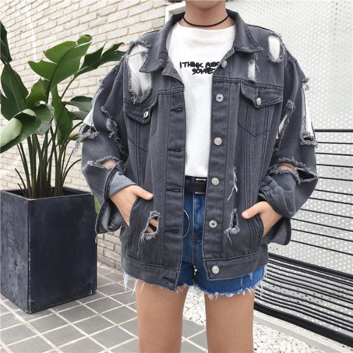 ripped oversized grey denim jacket, with many holes, 90s grunge fashion, worn by a slim woman, in a white t-shirt with black print, and blue denim cutoff shorts
