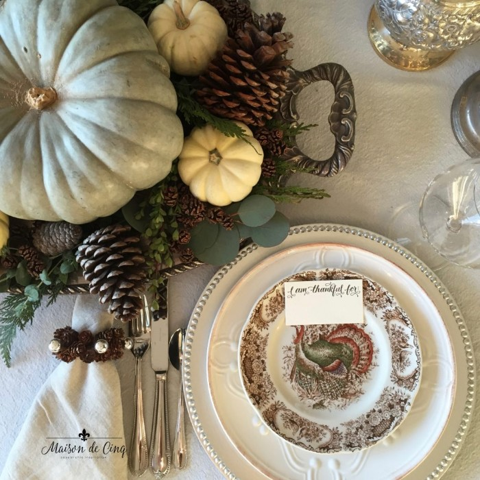 pinecones in different sizes, a pale duck's egg blue pumpkin, surrounded by small white pumpkins, and green leaves, on an ornamental silver dish, thanksgiving centerpiece, placed near three stacked dishes, silver cutlery and a whte napkin