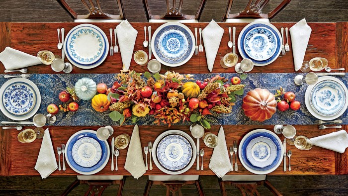 wooden rectangular table, with eight plates, in white and blue, white napkins and silver cutlery, decorative pumpkins and fall leaves, thanksgiving dinnerware