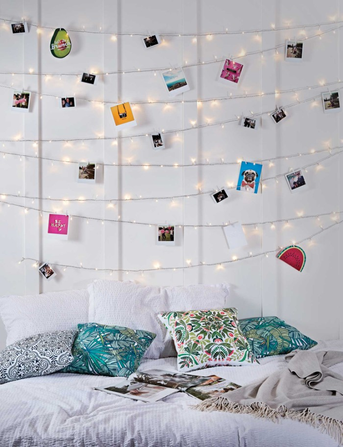 lit string lights, hung on a white wall, and decorated with polaroid photos, and small colorful images, cheap ways to decorate a teenage girl's bedroom, bed with three pillows, and four cushions