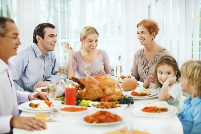 parents and two children, and two grandparents, sitting around a table, thanksgiving text messages, roasted turkey and other dishes