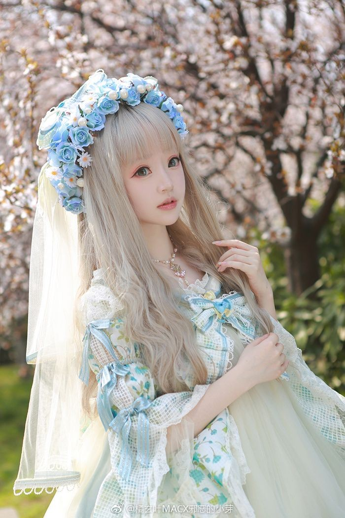 baby blue and white dress, with lace and frills, decorated with ribbons and bows, lolita fashion, worn by a girl, in a long platinum blonde wig, with faux flowers and a veil