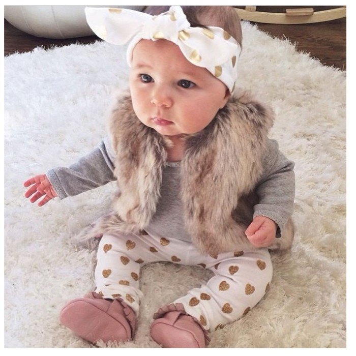 stylish baby girl thanksgiving outfit, white trousers with gold hearts, pale grey jumper with long sleeves, faux fur gilet, and a white and gold headband