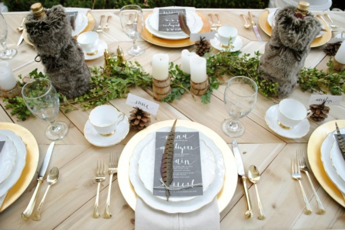plush dark grey bottle holders, on a festive table, with gold and white plates, topped with black menu cards, and spotted feathers, thanksgiving tablescape, candles and green decorative folliage