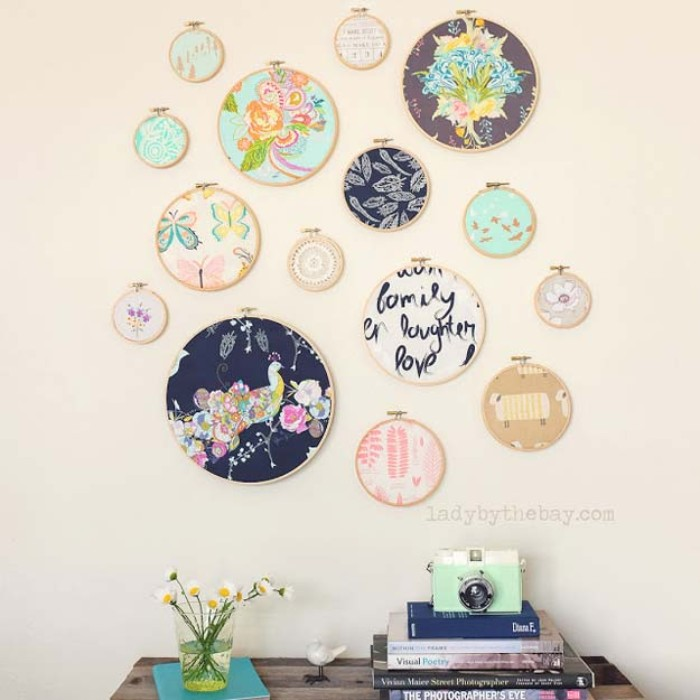 embroidery circles made of wood, featuring pieces of fabric with different prints, and in different colors, hung on a pale cream wall, over a small wooden table