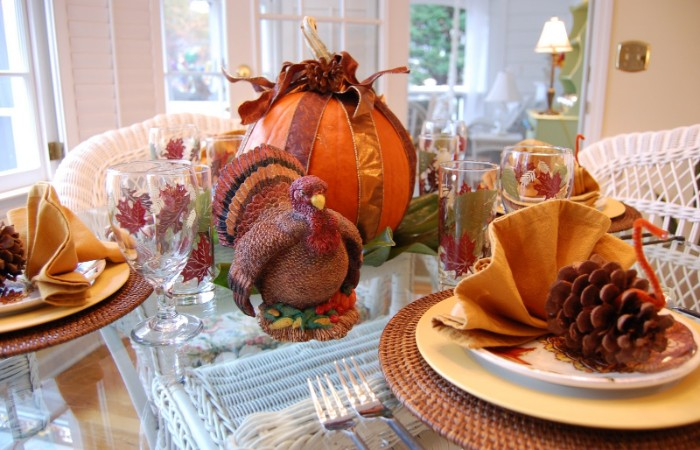 bird figurine in brown and orange, on a glass table, with plates and a large pumpkin, tied with ribbons, turkey decorations made from pinecones, orange pipe cleaners, and yellow napkins