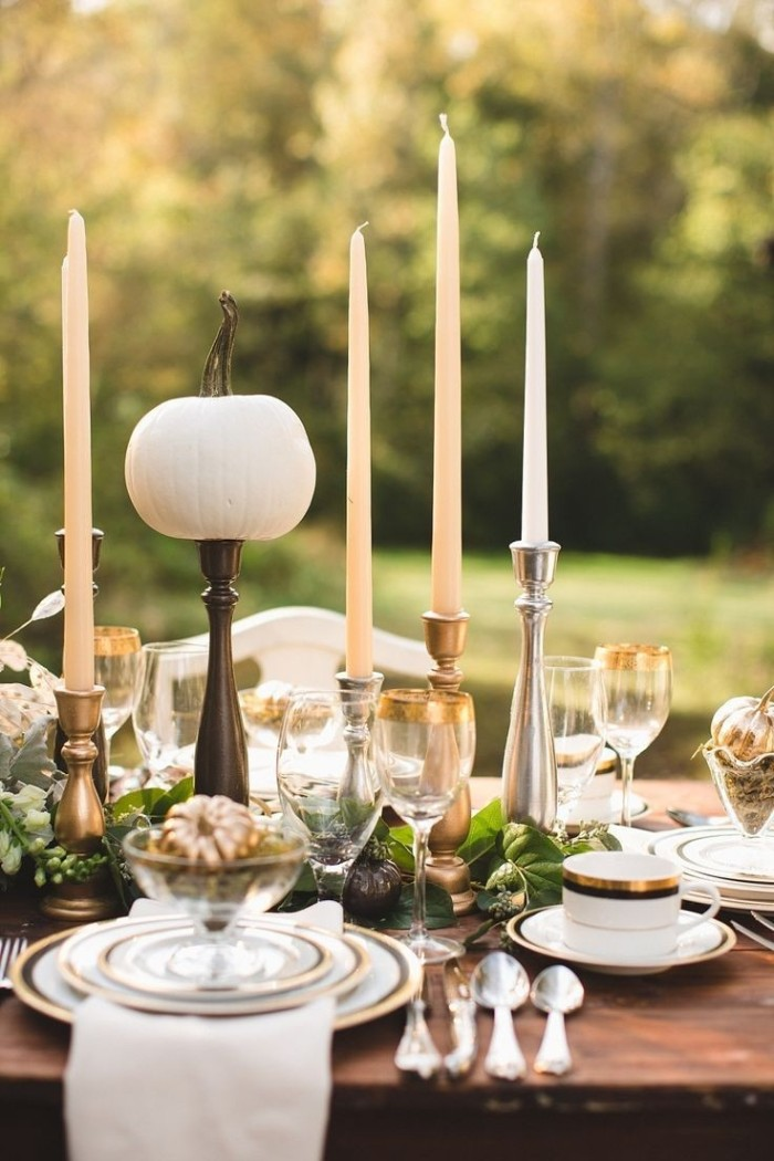 boho style thanksgiving dinnerware, gold-rimmed dishes and glasses, tall cream and white candles, on a dark brown wooden table, decorated with pumpkin ornaments, and placed in a garden
