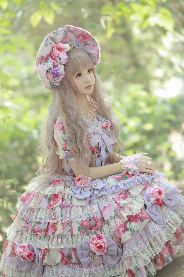tiered dress with lace incerts and flounces, featuring a floral pattern, in pink and green, lolita fashion on a girl, wearing a florak bonnet, with faux flowers, and a long ash blond wig