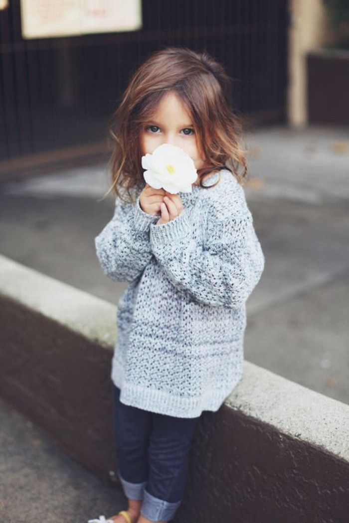 chestnut brown shoulder length hair, on a small child, dressed in an oversized, grey knitted jumper, girls thanksgiving outfit, skinny dark blue jeans