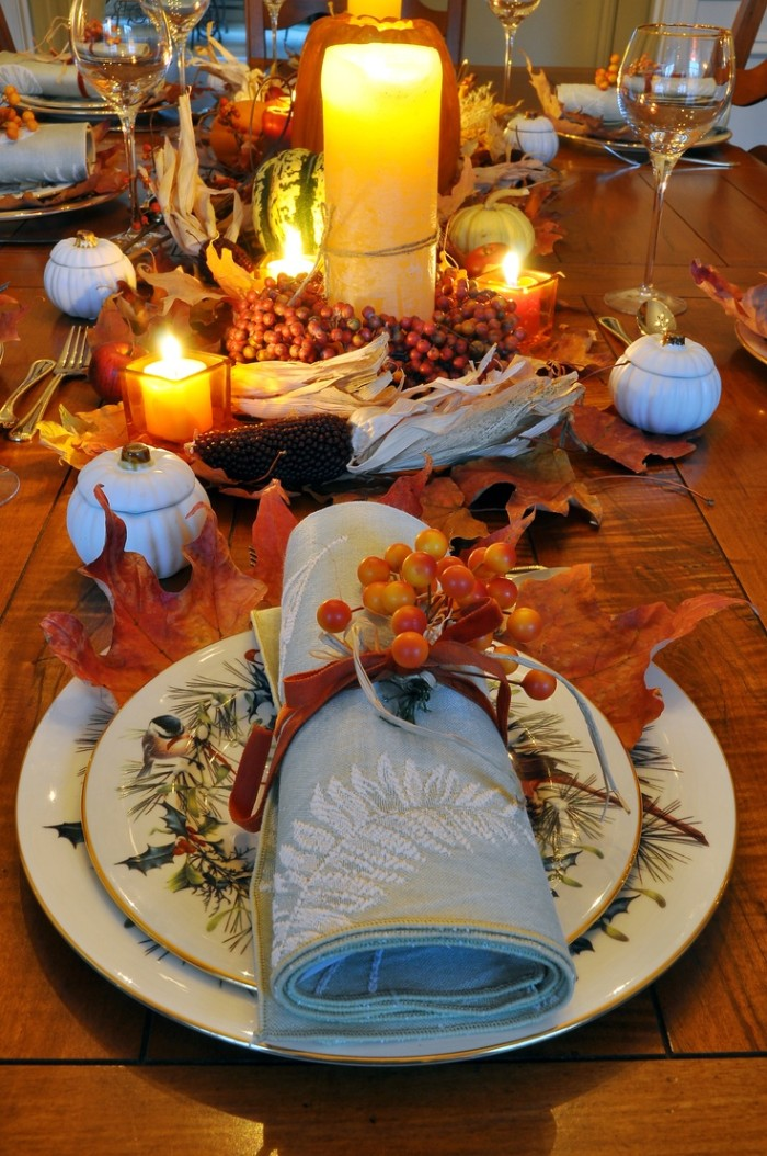 rolled up pale blue napkin, with a white botanical embroidery, tied with an orange ribbon, and decorated with small, yellow and orange berries, on top of two stacked plates, fall leaves and lit candles