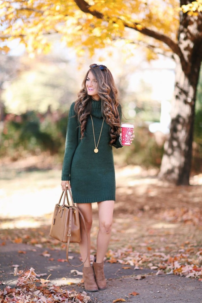 laughing brunette woman, wearing a dark green, turtle neck jumper dress, and beige suede ankle boots, she is holding a matching beige leather bag, and a red coffee cup