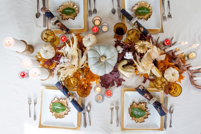 square yellow and white plates, with place holders, on a white tablecloth, decorated with a pale, duck's egg blue pumpkin, thanksgiving centerpiece, surrounded by fall leaves, dried corn leaves, candles and smaller white pumpkins