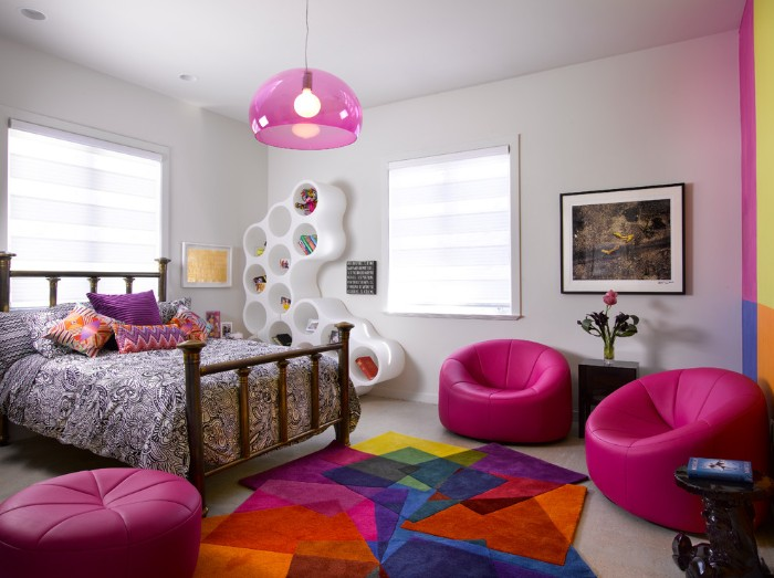 ottomans in fuchsia pink, in a room with a bed, covered in multicolored cushions, cute teen rooms, multicolored rug and a framed painting