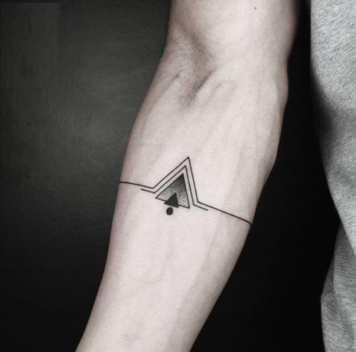 lines and triangles, in black and grey, and a single black dot, symmetrical cool arm tattoos, on the inside part of a man's arm, just below the elbow