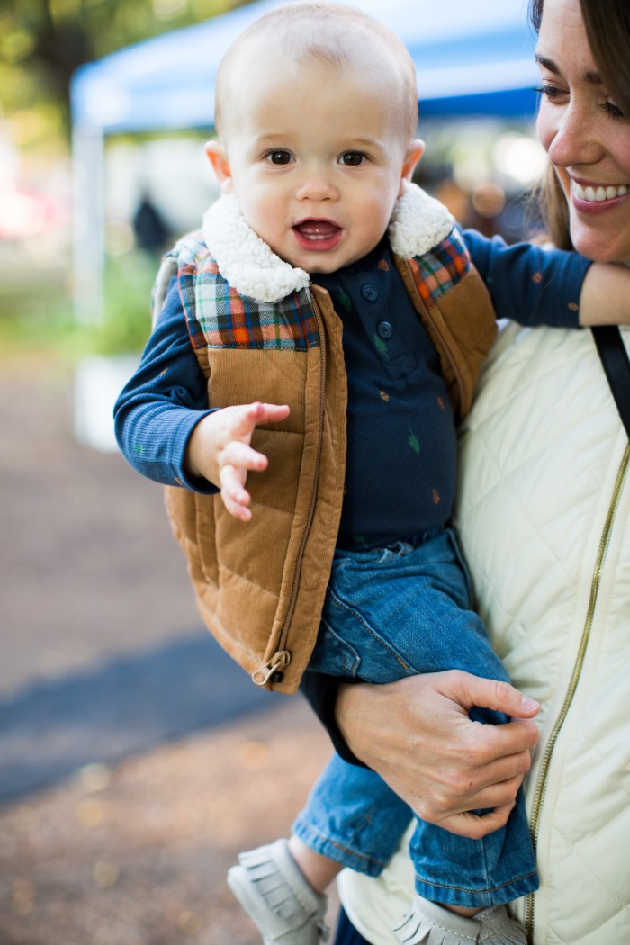 baby thanksgiving outfits, dark navy jumper, and blue jeans, on a small baby boy, wearing a beige gilet, with a white sherling fur trim, and plaid details