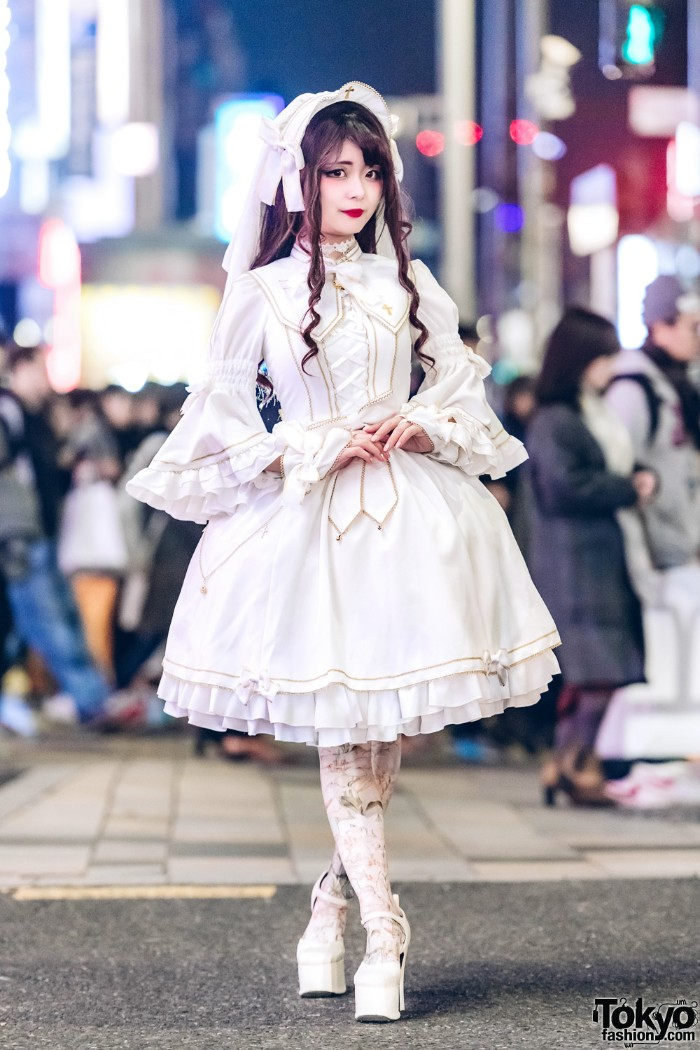 white dress with bell-shaped sleeves, a corset-like lace-up detail, and a large collar, featuring gold details, and cross motifs, define lolita, on a girl, wearing a brunette wig