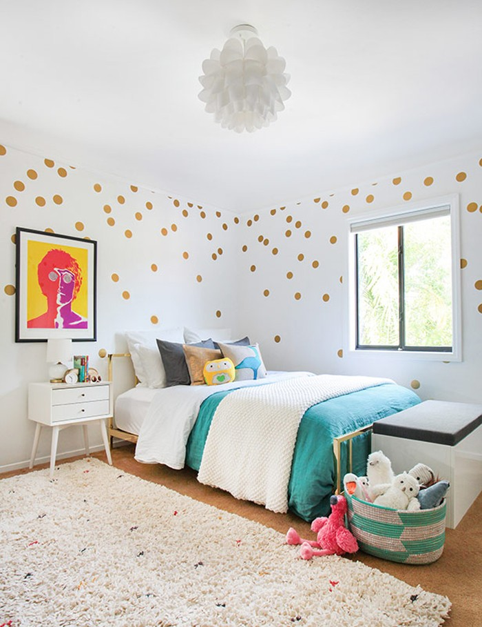 pop art style image, in a black frame, hanging on a white wall, decorated with gold dots, in a room with a bed, a window and a fluffy pale beige rug