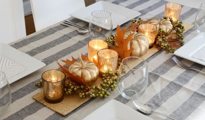 spray-painted faux pumpkins, in metallic gold, surrounded by tea lights, orange fall leaves and small green berries, thanksgiving centerpiece, on a grey and off-white tablecloth, with large square white plates