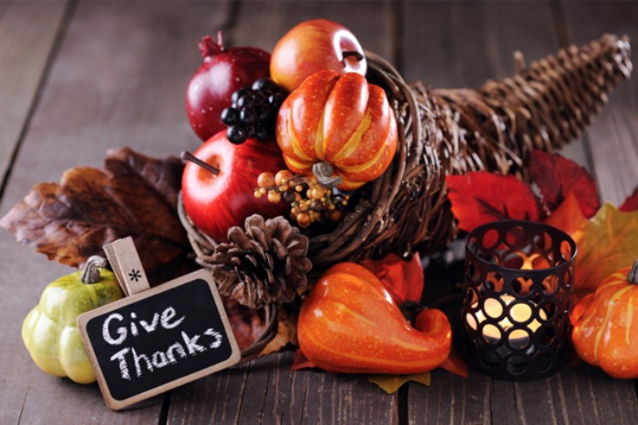 give thanks written in white chalk, on a small black and beige sign, placed near a horn of plenty decoration, filled and surrounded by small faux pumpkins, fall leaves and apples, gourds an pine cones