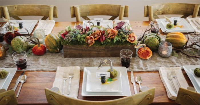 thanksgiving centerpiece, small and narrow wooden crate, filled with green plants, and orange flowers, surrounded by pumpkins, gourds and dried branches, on a wooden table with square, white plates